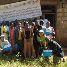 smiling group of farmers and researchers outdoors, in front of school house with usaid logo banner